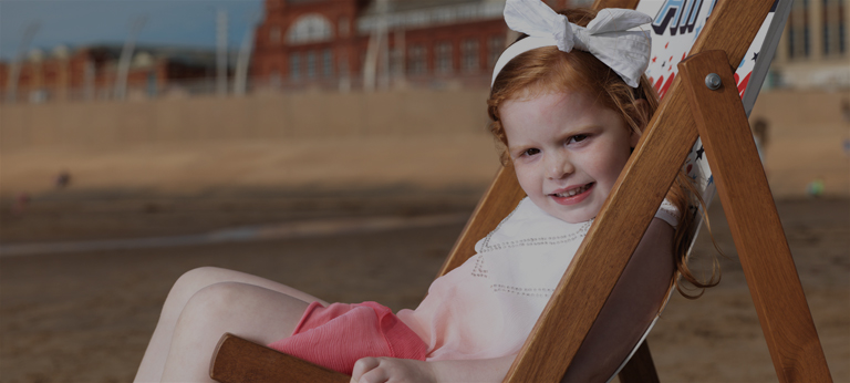 Young girl sat in deck chair.
