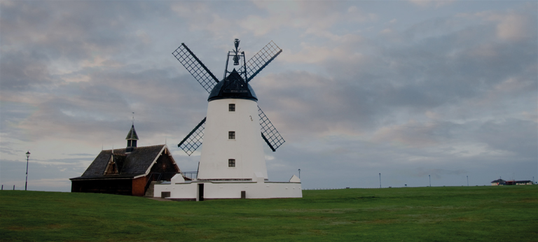 Windmill and building on lawn.