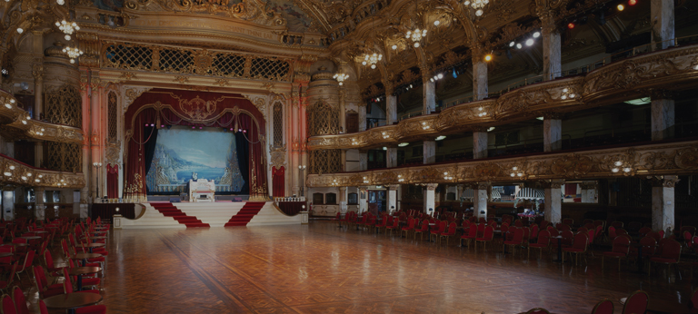 Ornate ballroom with balconies and stage.