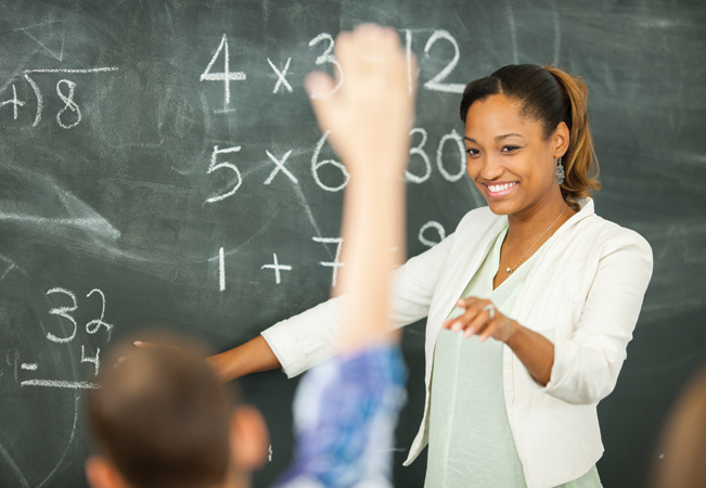 Teacher pointing to child, blackboard behind with sums on.
