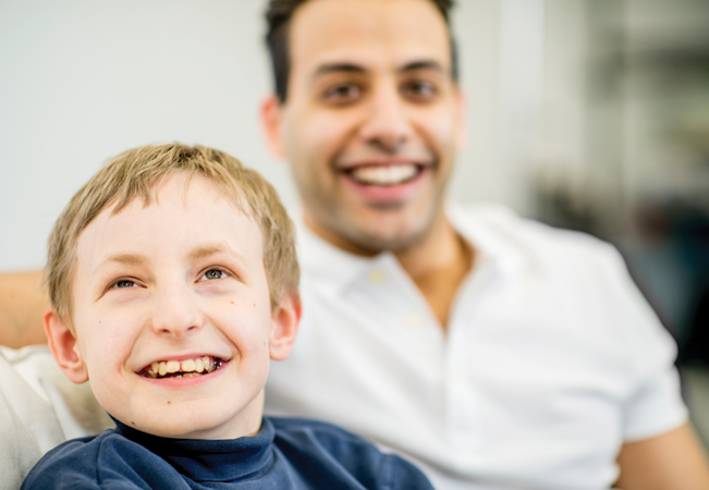 Boy sat on settee smiling with smiling man behind.